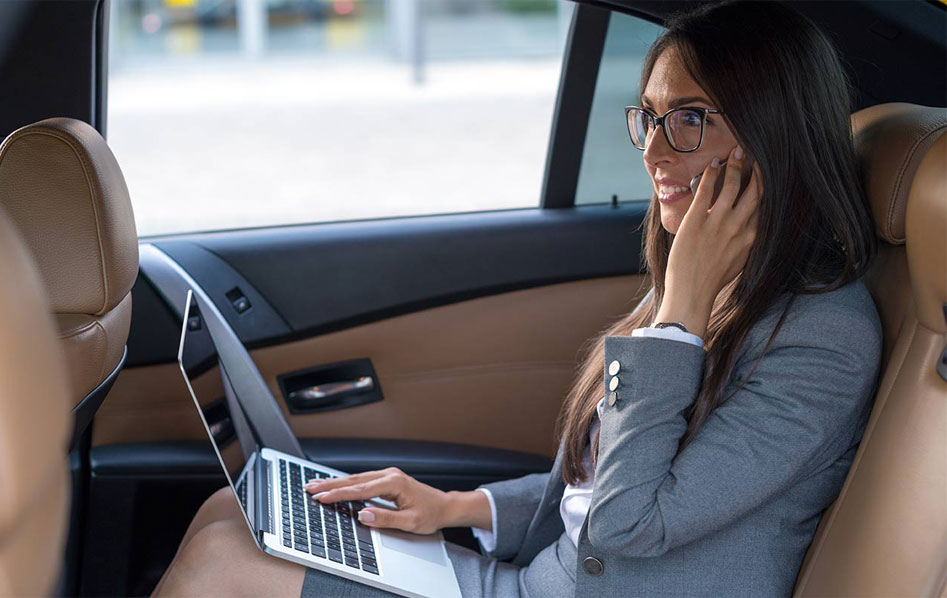 una signora mentre parla al telefono con il pc sulle ginocchia mentre è in macchina