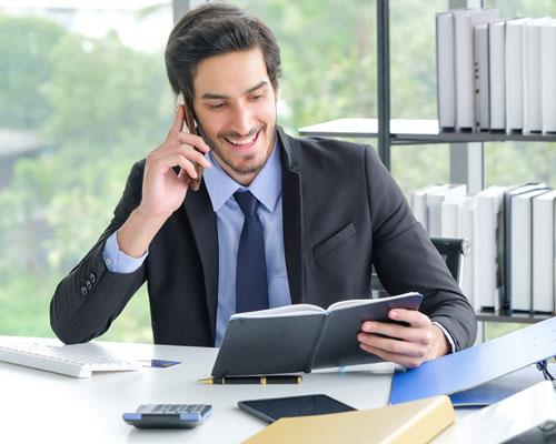 un uomo al lavoro mentre parla al telefono guardando l'agenda