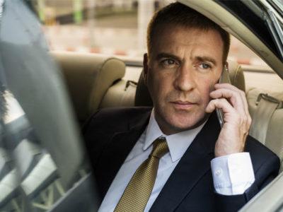 uomo d'affari parla al telefono mentre guarda fuori dal finestrino dell'auto