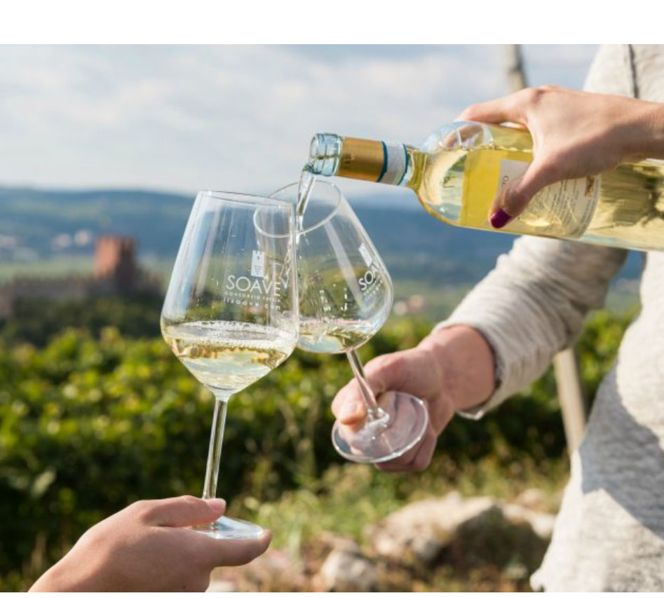 due calici mentre gli viene versato il vino bianco soave